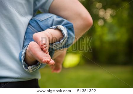 Bare feet of a cute baby on the summer background. Childhood in the farm. Small bare feet of a little baby girl. Father holding baby. Man with a child in the summer park.