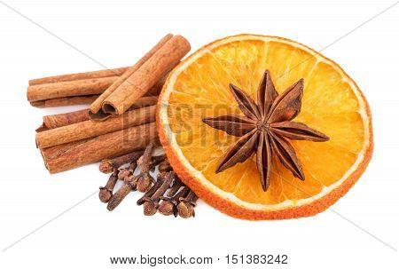 Christmas spices decoration. Cinnamon sticks cloves and orange slices on white.