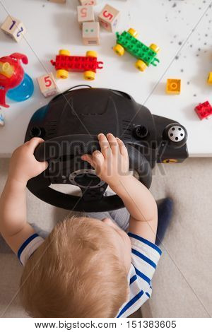 Top view on cute toddler boy sitting on the sofa and playing with computer steering wheel. Future driver. Getting ready for professional driving. Child driving a car. Funny boy indoors. Boy and a car.