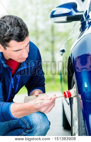 Man cleaning the alloy wheel hub of his car suing a soft bristle brush and soap to get between the spokes