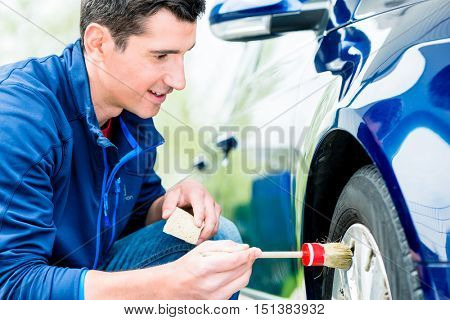 Smiling attractive man cleaning the alloy hubs on his car tyres using a soft bristle brush and soap
