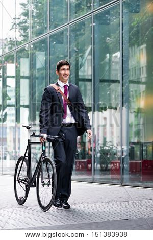 Businessman wheeling a bicycle through town along a pedestrian walkway as he commutes to work using eco-friendly transport