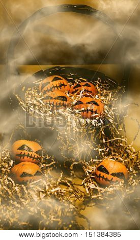 Scary dead pumpkins heads in a misty horror scene of halloween decorating madness. Mandarin freaky fruits