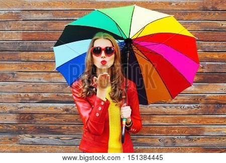 Fashion Pretty Woman With Colorful Umbrella Sends Air Sweet Kiss In Autumn Day Over Wooden Backgroun