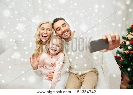 christmas, holidays, technology and people concept - happy family sitting on sofa and taking selfie picture with smartphone at home