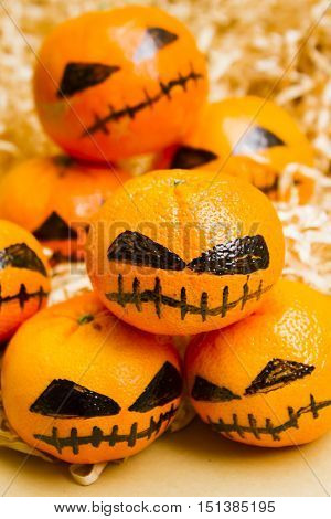 Holiday still life decoration on a group of clementine oranges disguised as evil pumpkins. Halloween craft treats