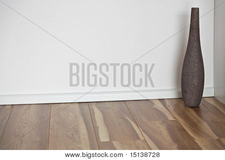 wooden floor with white wall and vase