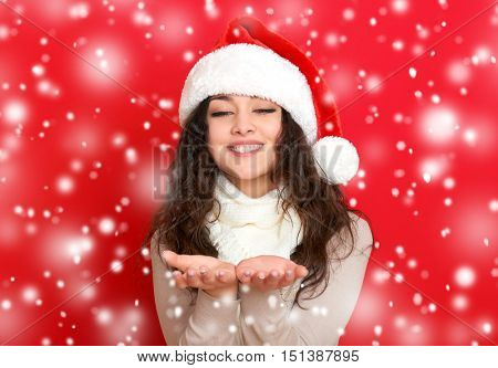 girl in santa hat portrait on red color background, christmas holiday concept, happy and emotions