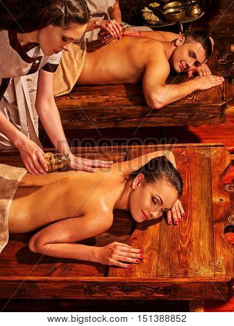 Couple in love having oil Ayurveda spa treatment on wooden bed. India exotic relaxing treatment .