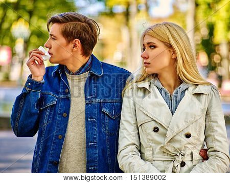 Man with cold rhinitis on autumn outdoor. Fall flu season. Girl looks with compassion on suffering of loved one. During autumn season lot of people suffer from allergies and disease.