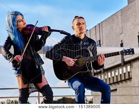 Couple of buskers with girl violinist and man guitarist on blue sky on roof outdoor.