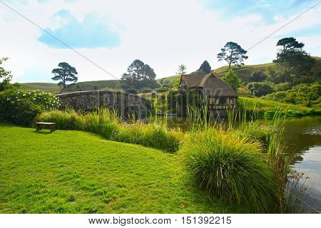 Matamata, New Zealand - January 15, 2015: Hobbits Mill And Bridge Reflecting In Small Pond
