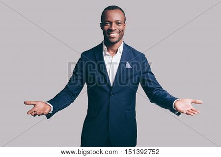 You are welcome! Handsome young African man in smart casual jacket gesturing and smiling while standing against grey background
