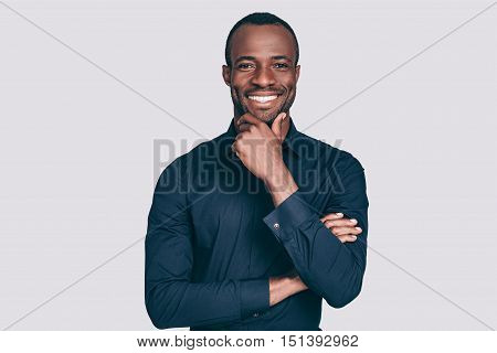 Always in good mood. Handsome young African man holding hand on chin and looking at camera with smile while standing against grey background