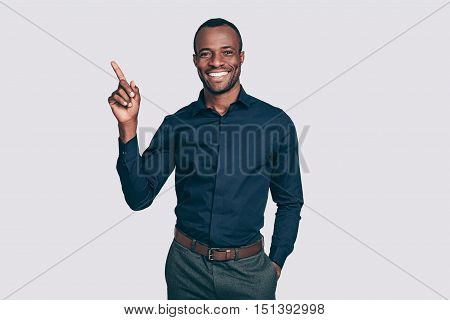 Look at this! Handsome young African man pointing up and smiling to you while standing against grey background