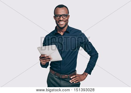 Always ready to help. Handsome young African man holding digital tablet and looking at camera with smile while standing against grey background