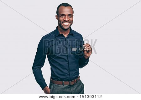 Young and successful. Handsome young African man carrying eyeglasses and looking at camera with smile while standing against grey background