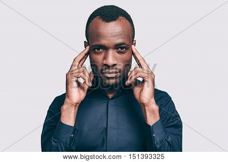 Feeling stressed. Frustrated young African man holding fingers on head and looking at camera while standing against grey background