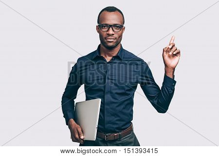 Expert advice. Handsome young African man carrying laptop and looking at camera while standing against grey background