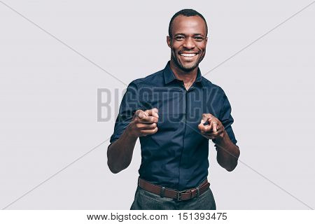 Choosing you. Handsome young African man pointing you and smiling while standing against grey background