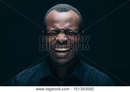 Making a face. Portrait of young African man making a face while keeping eyes closed and being in front of black background