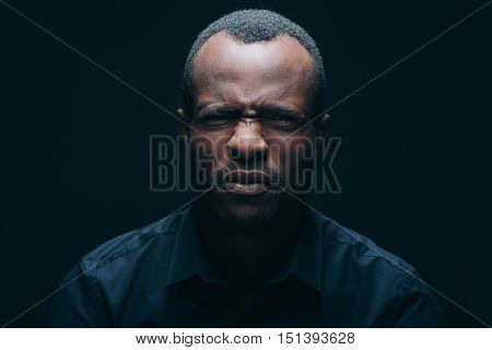 This is disgusting! Portrait of young African man looking at camera and expressing disgust while being in front of black background