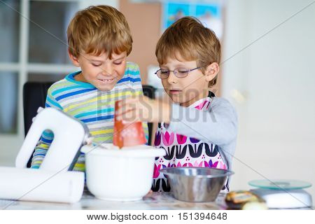 Two little funny twins brothers baking apple cake in domestic kitchen. Kid boys having fun with working with mixer, eggs and honey