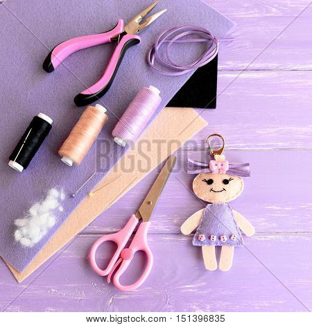 Creative art and craft idea for kids. Felt doll keychain, scissors, thread, needles, pins, suede cord, pliers, felt sheets on wooden background. Set to create kids keychain. Top view