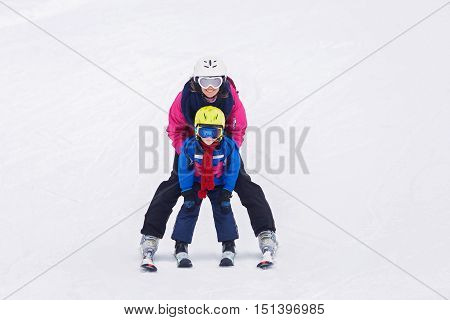 Sweet Young Boy And His Mother, Learning To Ski On A Mild Ski Slope In Austrian Ski Resort