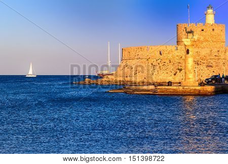 View of the historic Mandraki Harbour with St. Nicholas Fortress before sunset on the Island of Rhodes, Greece