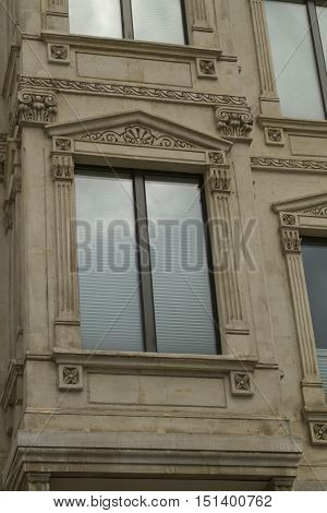 Architectural details and decoration of the vintage facade framing the windows