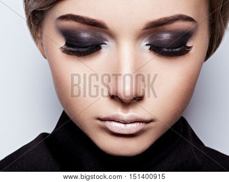 Closeup woman  face with long black lashes. fashion makeup. Beautiful woman face with  black mascara.