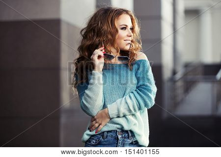Happy young stylish woman with sunglasses on city street. Female fashion model with long curly hairs outdoor