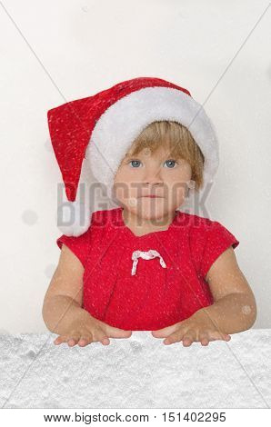 girl in Santa suit in falling snow on gray background