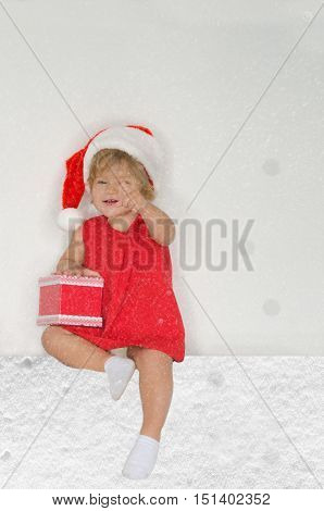 girl in Santa suit with snowflakes with gift on gray background
