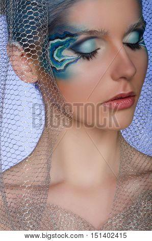 woman with face art mermaid with blue background