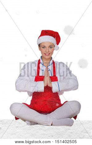 chef in hat of Santa Claus doing yoga with snow on white background