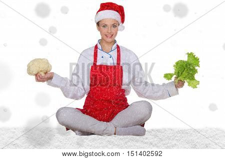 Woman cook in Santa hat yoga vegetables under snow on white background