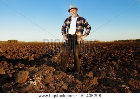An elderly farmer standing in a plowed field. Agriculture, crop concept.