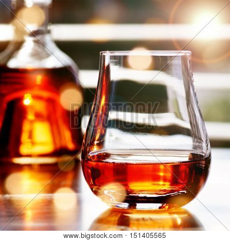 Whisky in a bottle with glass in front of a window with sun reflexes