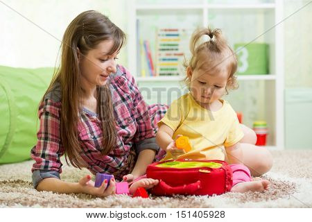 baby with mother playing with educational toy