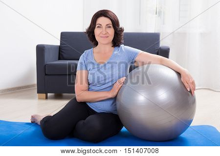 Slim Sporty Mature Woman With Fitness Ball At Home