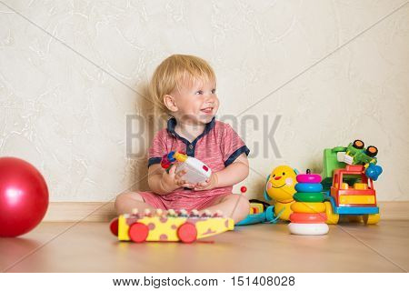 Portrait of a beautiful baby boy on the floor with music toys. 15 year-old child playing with educational cup toys at home. Little blond kid with blue eyes is playing with toy at home indoors
