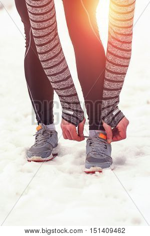 Young male runner tying his shoelaces outdoors in winter nature. Fitness, running, jogging workout.