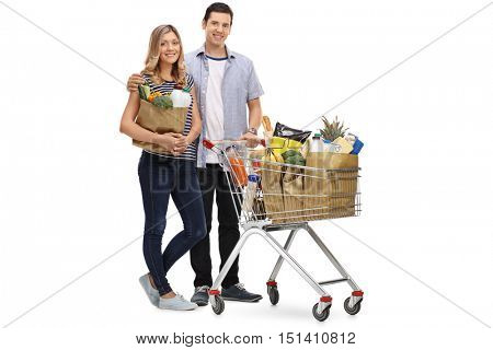 Full length portrait of a young couple posing with a shopping bag and a shopping cart isolated on white background