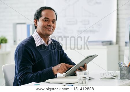 Portrait of smiling Indian businessman working on digital tablet