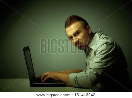 Young dissatisfied man working with laptop.