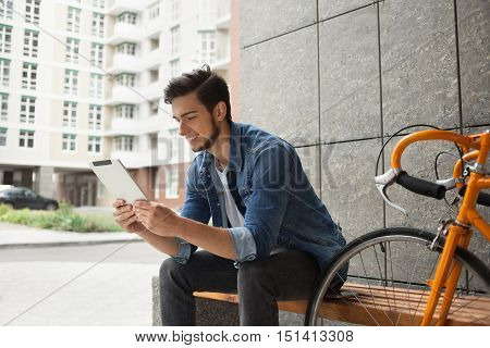 Guy in denim jacket with beard and orange bicycle sitting on a bench looking at the tablet on the background of buildings