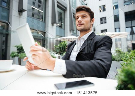 Portrait of handsome young businesman with tablet and blank screen mobile phone in outdoor cafe
