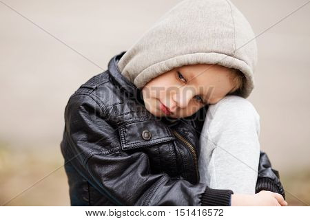 Portrait Of Sad Little Boy Wearing Black Leather Jacket And Hoodie Outdoors